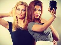 Deux filles de modèles prenant la photo d'individu avec l'appareil-photo Images libres de droits