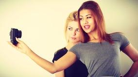 Deux filles de modèles prenant la photo d'individu avec l'appareil-photo Photo libre de droits