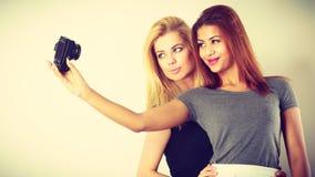 Deux filles de modèles prenant la photo d'individu avec l'appareil-photo Photographie stock libre de droits