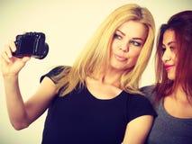 Deux filles de modèles prenant la photo d'individu avec l'appareil-photo Images stock