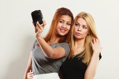 Deux filles de modèles prenant la photo d'individu avec l'appareil-photo Photographie stock