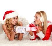 Deux filles de Noël sur le tapis blanc, avec des présents Image libre de droits