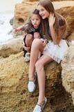 Deux filles de petite soeur s'asseyant sur la plage Photos libres de droits