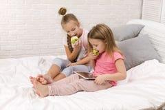 Deux filles de petits enfants jouent dans la chambre à coucher image stock