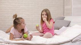 Deux filles de petits enfants mangent les pommes fra?ches vertes banque de vidéos