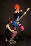 Deux filles de roche, l'un d'entre eux léchant la guitare Photographie stock libre de droits