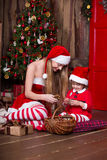 Deux filles de Santa décorant l'arbre de Noël ayant l'amusement Intérieur de nouvelle année L'atmosphère de Noël, famille célébra Photo stock