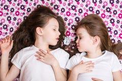 Deux filles de sommeil et un réveil blanc dans l'intervalle photos libres de droits