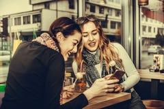 Deux filles de sourire à l'aide du smartphone et buvant du café Photos libres de droits