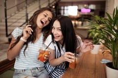 Deux filles de sourire assez jeunes, habillées dans l'équipement occasionnel, s'asseyent l'un à côté de l'autre et regarder la ca photos stock