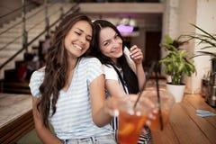 Deux filles de sourire assez jeunes, habillées dans l'équipement occasionnel, s'asseyent l'un à côté de l'autre et regarder la ca image libre de droits