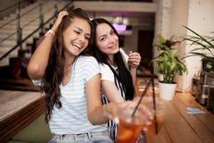 Deux filles de sourire assez jeunes, habillées dans l'équipement occasionnel, s'asseyent l'un à côté de l'autre et regarder la ca photo stock