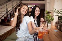 Deux filles de sourire assez jeunes, habillées dans l'équipement occasionnel, s'asseyent l'un à côté de l'autre et regarder la ca images stock