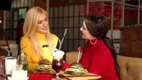 Deux filles de sourire boire des cocktails et manger des hamburgers dans un restaurant lumineux banque de vidéos