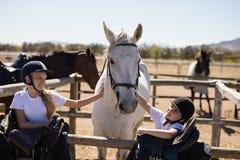 Deux filles de sourire caressant le cheval Photographie stock