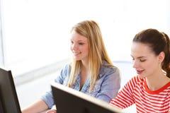 Deux filles de sourire dans la classe d'ordinateur Photos stock