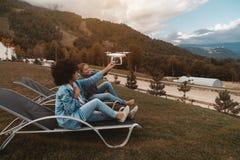 Deux filles de sourire de différentes courses tenant le bourdon de vol photo libre de droits