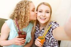 Deux filles de sourire faisant le selfie en café Image stock