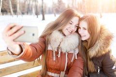 Deux filles de sourire font le selfie en parc d'hiver Photographie stock