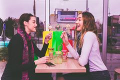 Deux filles de sourire mangeant des gâteaux et parlant en café Photographie stock libre de droits