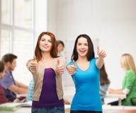 Deux filles de sourire montrant des pouces  Photographie stock libre de droits