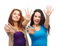 Deux filles de sourire montrant leurs paumes Photos libres de droits