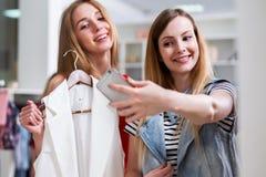 Deux filles de sourire prenant le selfie tout en faisant des emplettes dans un magasin d'habillement Photo stock