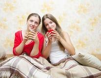 Deux filles de sourire prennent le thé Images libres de droits