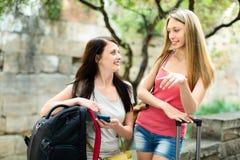 Deux filles de sourire trouvant le chemin avec le smartphone Photo libre de droits