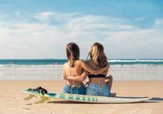Deux filles de surfer à la plage Photos stock