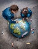 Deux filles dessinant l'image réaliste de la terre avec des craies sur la terre Photo stock