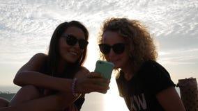 Deux filles emballées mélangées de sourire montrent des photos sur le smartphone Hd occasionnel de mode de vie au ralenti banque de vidéos