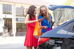 Deux filles empilent les sacs dans le véhicule Photos stock