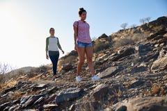 Deux filles en bonne santé marchant sur le flanc de coteau Photographie stock
