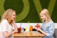 Deux filles en café avec le présent Images libres de droits