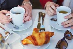 Deux filles en café extérieur parisien, café potable avec le croissant Image libre de droits