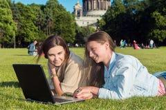Deux filles en parc avec un ordinateur portable Photographie stock libre de droits