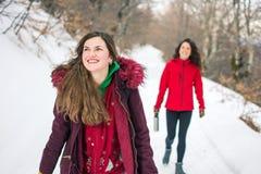 Deux filles en voyage de hausse sur la montagne neigeuse Photos stock