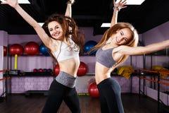 Deux filles enthousiastes de forme physique sautant au centre médico-social Image stock