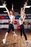 Deux filles enthousiastes de forme physique sautant au centre médico-social Photo stock