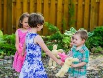 Deux filles et deux garçons jouant Ring Around le Rosie images libres de droits