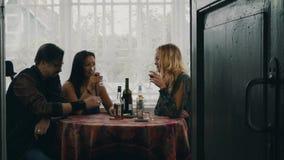 Deux filles et homme causant à la table Alcool de boissons sur la terrasse de la maison de campagne clips vidéos