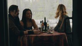 Deux filles et homme causent à la table avec des boissons sur la terrasse de la maison de campagne heureux banque de vidéos