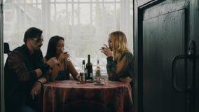 Deux filles et homme parlant à la table Alcool de boissons sur la terrasse de la maison de campagne clips vidéos