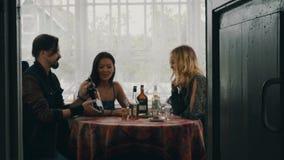 Deux filles et homme parlant à la table Vin de boissons sur la terrasse de la maison de campagne banque de vidéos