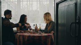 Deux filles et homme parlant à la table Vin rouge de boissons sur la terrasse de la maison de campagne clips vidéos