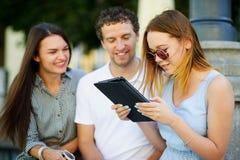 Deux filles et le type avec l'intérêt regardent l'écran de comprimé Images libres de droits