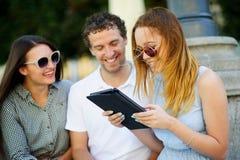 Deux filles et le type avec l'intérêt regardent l'écran de comprimé Photo libre de droits