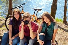 Deux filles et un homme prenant des photos de photo sur les coas sauvages de rivière Image stock
