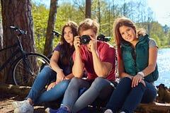 Deux filles et un homme prenant des photos de photo sur les coas sauvages de rivière Images libres de droits